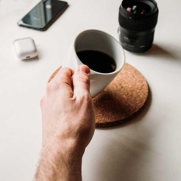 Close up of a man's hand holding a white mug of black coffee.