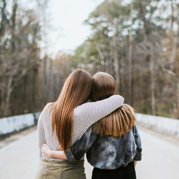 Medium shot of two young ladies hold each other in embrace facing away from the viewer. They are leading into each other and walking along a path.
