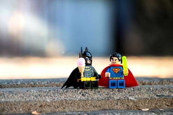 Batman and Superman as Lego figurines sit on a street curb eating ice cream.