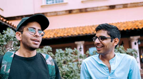 Two young men are in conversation in a beautiful Mediterranean courtyard. Both dressed casually. Both with glasses. They are smiling.