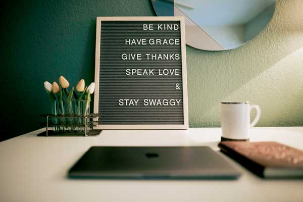 "A workspace with a closed laptop, tulip flowers, brown embossed journal, gold rimed white mug highlights a sign that says the encouraging words, ""Be kind, have grace, give thanks, speak love, and stay swaggy."
