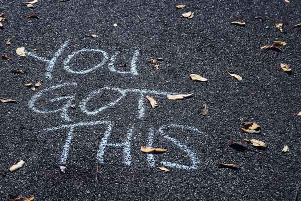 "Close up of pavement with scattered leaves. A light blue chalk written words of encouragement read, ""You got this."""